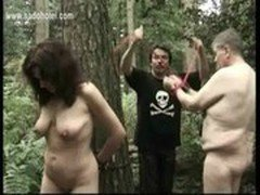 Naked slave tied to a tree got her pierced pussy played by master while her husband is watching